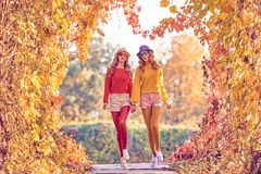 Fall Fashion. Urban Outdoor. Woman Walking in Park. Fall Fashion. Two Young Woman Jumping Having Fun in Autumn Park. Urban Outdoor. Beautiful Girl Sisters Happy Royalty Free Stock Image