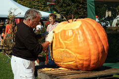 Fall Fest Pumpkin Carver - Frankfort, Michigan. Ed Moody, pumpkin carver, carving a pumpkin at the Benzie County Fall Fest in 2008, in Frankfort, Michigan.  The Stock Images