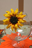 Fall flower. Yellow fall flower on a glass with fall leaf under Stock Photo