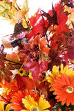 Fall Flowers. Closeup view of some fake fall flowers and leaves along with a small scarecrow, isolated against a white background Royalty Free Stock Image