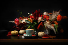 Autumn bouquet on black background with copy space. Fall flowers bouquet background on black. Colorful and warm autumn composition with cappuccino, pumpkins on stock images