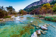 Fall foliage on the crystal clear Frio River in Texas. Fall Foliage on Trees Lining the Rocky, Emerald, Crystal Clear Frio River at Garner State Park, Texas Stock Image