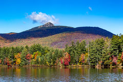 Fall foliage on the lake with mountain backdrop in New Hampshire. Fall foliage on New Hampshire pond with mountain in the background Royalty Free Stock Photography