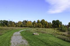 Autumn foliage along a gravel hiking trail through a field. Fall foliage in October. Sunny morning in the park. Black Creek Park Rochester, NY royalty free stock photography