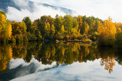 Fall foliage reflected in calm water. Low lying clouds break up to reveal brilliant fall foliage reflecting on calm waters of the Easton Ponds in the Cascade Royalty Free Stock Photos