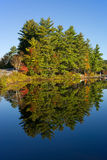Fall foliage reflected on lake in Maine Royalty Free Stock Photo