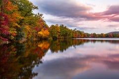 Fall foliage reflects in Hessian Lake. At sunset, near Bear Mountain, NY royalty free stock images
