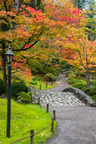 Fall Foliage Stone Bridge. Walking path with stone bridge winding through trees autumn colors. Vertical stock image