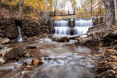 Fall foliage and waterfalls. Water spilling over a old dam during Fall Foliage royalty free stock images