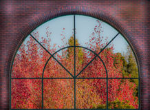 Fall Foliage Window. The view through a large, arched window in a brick wall to trees in orange and red Fall colors Stock Photos