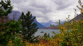 Fall Framed Wild Goose Island. Seen through Pines and Autumn foliage, Wild Goose Island seem to float on the choppy water of St Mary Lake.  Gloomy storm clouds Royalty Free Stock Photo