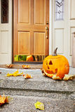 Fall front door. Front steps and open front door with fall leaves and jack-o-lantern Royalty Free Stock Photos