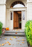 Fall front door. Front path, steps and open front door with fall leaves and jack-o-lantern Stock Image