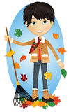 Fall fun with boy. Boy raking leaves while leaves blow in the wind around him Royalty Free Stock Images
