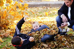 Fall Fun. Father and two sons frolic in the leaves Royalty Free Stock Photos