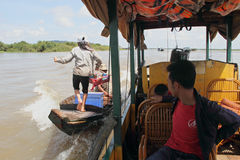 Fall Girl Hawking With Boat. A Vietnamese girl jumping from a tourist boat holding cold drinks in her hand. The girl is selling cold drinks to the tourist by stock photography
