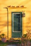 Fall: green door with pumpkins. New England yellow house with green door and decorative pumpkins Royalty Free Stock Photos