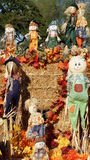 Fall and Halloween decorative dolls. A beautifully made Fall and Halloween collection of smiling decorative dolls (characters) sitting around bales of straw at Stock Photography