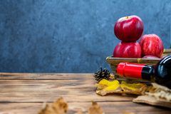 Fall harvest cornucopia. Basket with red apple and wine on the table. Royalty Free Stock Photography