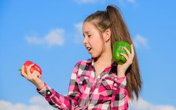 Fall harvest homegrown vegetables. Vegetarian concept. Which pepper would you pick. Kid girl hold red and green peppers. Sky background. Child presenting kinds stock photography