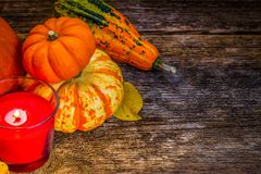 Fall harvest of pumpkins. With candle on wooden table, retro toned Stock Image