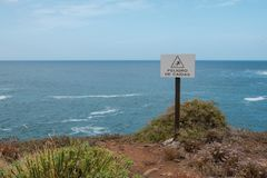 Fall hazard spanish: Peligro De Caidas warning sign with ocean. Landscape background royalty free stock photography