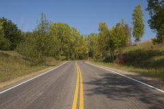 Fall Highway Scenic. A two lane highway passes by trees and curves around a hill in early fall Royalty Free Stock Images