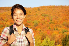 Fall hiking woman in autumn forest. Female hiker looking around in forest in autumn colors. Beautiful young woman on hike Stock Image