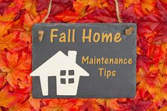 Fall Home Maintenance Tips with a chalkboard with a wood house. And fall leaves royalty free stock photo
