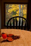 Fall inside and out. A photo of a dining table decorated for fall with fall colors on a tree outside the picture window behind the table royalty free stock photos
