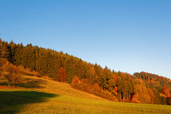 Fall landscape rolling hills and forest in sunset colors. The soft sunlight shines on a hill with its trees by autumnal coloring - Indian summer in Germany Royalty Free Stock Image