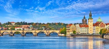 Fall landscape view to Charles bridge on Vltava river in Prague Czech republic with blue sky and withe clouds. Royalty Free Stock Images