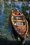Fall of the leaf. Canal and boat, covered with autumn leaves, a bright sunny noon Stock Image