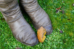 Fall leaf rests on a woman's winter boots Stock Photo