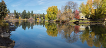Fall leaves and the Deschutes River. Colorful autumn leaves and the Deschutes River at Mirror Pond in Bend, Oregon Stock Photo