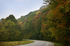 Fall leaves line the curving road in rural Indiana. Stock Image