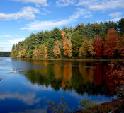 Fall leaves on a peninsula reflected in a lake Stock Images