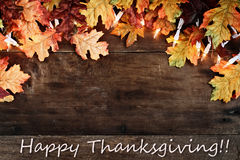 Fall Leaves and Text Happy Thanksgiving over Wooden Background. Rustic fall background of autumn leaves and decorative lights with Happy Thanksgiving text over a stock photos