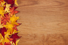 Fall leaves on wood grain background Royalty Free Stock Photography