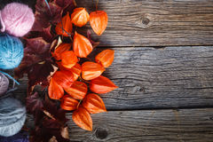 Fall leaves and wool clew  on rustic wooden background. Place for text Royalty Free Stock Photo