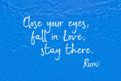 Fall in love blue Rumi. Close your eyes, fall in Love, stay there - ancient Persian poet and philosopher Rumi quote handwritten on blue wall Stock Photo