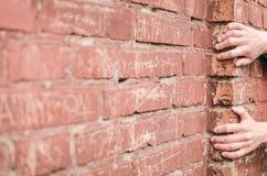 Fall Mann hält auf eine Leiste auf einer Backsteinmauer Lizenzfreie Stockfotos
