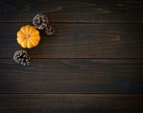 Fall Mini Pumpkin und Kiefern-Kegel in der unbedeutenden Stillleben-Karte auf schwermütigen, dunklen hölzernen Brettern Shiplap m stockfotos