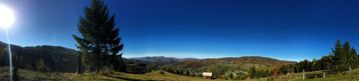 Autumn in the mountains, panorama of a mountainous landscape on the background of a blue sky. Autumn in the mountains, panorama of a mountainous landscape royalty free stock photography