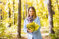 Fall, nature and people concept - Young beautiful woman in grey coat holding autumn bouquet of leaves stock photos