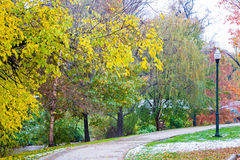Fall Path in the Park. Fall colors and a light dusting of snow line a path near Fourpole creek in Ritter Park, one of the United States top ten city parks Stock Images