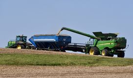 Combine Vaccum Loading Grain Cart. This is a Fall picture of a farmer harvesting his soybean crop, using the Combine Vaccum to load a grain cart in the field Royalty Free Stock Photos
