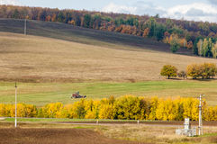 Fall plowed field, a large willow tree harvester mowing grass Stock Image