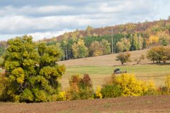 Fall plowed field, a large willow tree harvester mowing grass Stock Photo