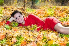 Fall. Portrait of beautiful young woman in autumn park. With maple leaves royalty free stock photography